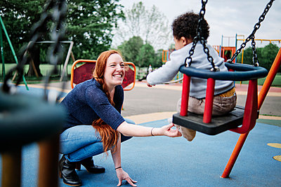 Mother tickling son sitting on swing in playground at park - p300m2287216 by Angel Santana Garcia