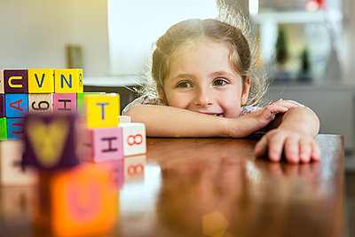 Smiling girl leaning on table at home - p300m2287550 by Stefanie Aumiller