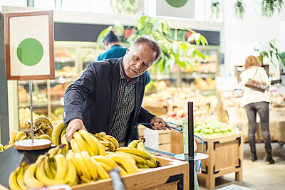Mature man buying bananas in organic supermarket - p426m1407411 by Kentaroo Tryman