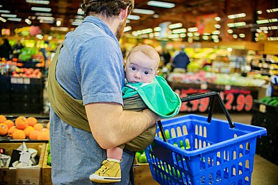 Father holding baby son and shopping basket in supermarket - p429m1047110 by Sue Barr