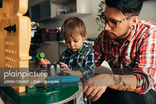 Father and son playing together on toy work bench - p300m1204691 by Zeljko Dangubic