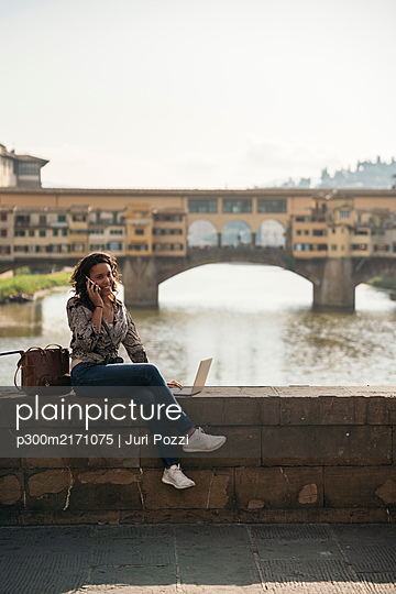 Young woman using laptop and cell phone on a bridge, Florence, Italy - p300m2171075 by Juri Pozzi