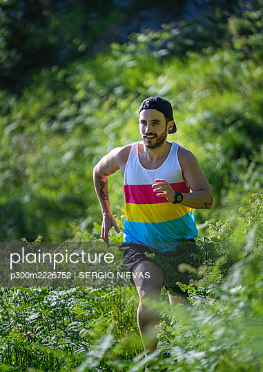 Sportsman looking away while running between grass on mountain at forest - p300m2226752 by SERGIO NIEVAS