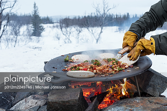 Preparing food over campfire - p312m2249746 by Michael Jönsson