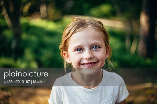 Portrait of cute smiling girl standing in forest - p426m2213197 by Maskot