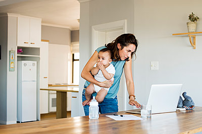 Woman using laptop computer while sitting with son at home - p1166m1226162 by Cavan Images