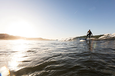 Man surfing on sea against clear sky during sunset - p1166m1414556 by Cavan Images