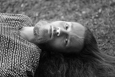 Junger Mann liegt im Grass Blick in die kamera - p1519m2124745 von Soany Guigand
