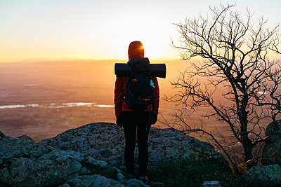 Spain, Catalunya, Girona, female hiker in the nature looking at view at sunrise - p300m1115056f by Bonninstudio