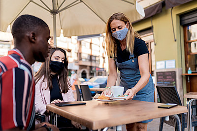 Waitress in face mask serving young couple at cafe during COVID-19 outbreak - p300m2220725 by Ezequiel Giménez