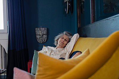 Senior woman staring while resting on sofa at home - p300m2265120 by Emma Innocenti