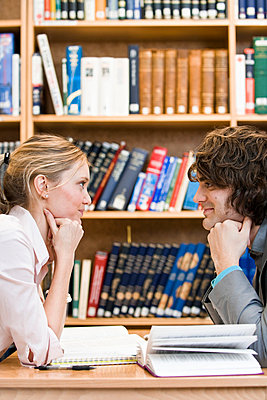 Two students sitting face to face in a library Sweden - p31222800f by Plattform