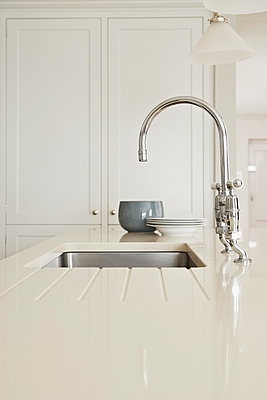 Chrome tap fitting and draining board with bowls,  kitchen detail - p349m896284 by Jon Day