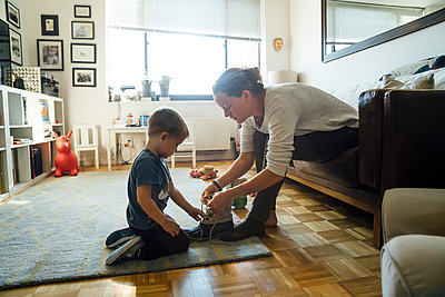 Mother teaching son to tie shoelace - p555m1231844 by Inti St Clair