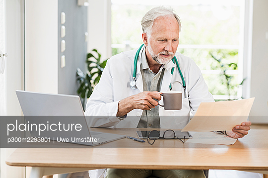 Male doctor having coffee while looking at medical report at desk - p300m2293801 by Uwe Umstätter