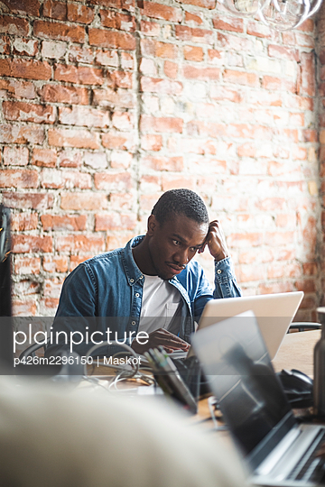Male entrepreneur using laptop while working in office - p426m2296150 by Maskot