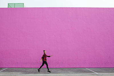 Full length of woman jumping on footpath against pink wall - p1166m1521682 by Cavan Images