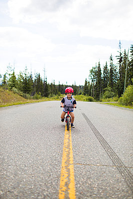 toddler boy biking on balance bike in middle of the road. - p1166m2147317 by Cavan Images