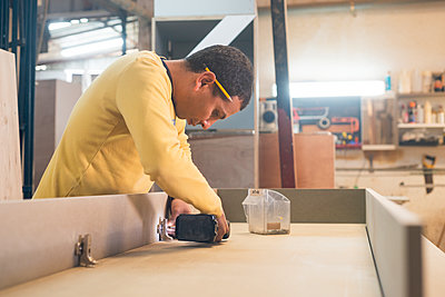 Carpenter working in workshop - p312m2208162 by Viktor Holm