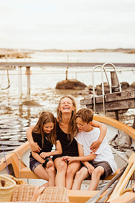 Smiling mother with arms around children sitting in boat at marina - p426m2238308 by Maskot
