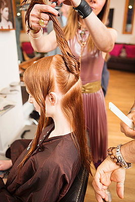 Female customer having long red hair twisted in hair salon - p429m1408083 by Nancy Honey