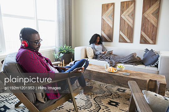 Couple relaxing listening to music with headphones and using digital tablet in living room - p1192m1201953 by Hero Images