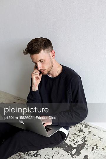Junger Mann mit Laptop Computer sitzt auf dem Fußboden - p1301m1582602 von Delia Baum