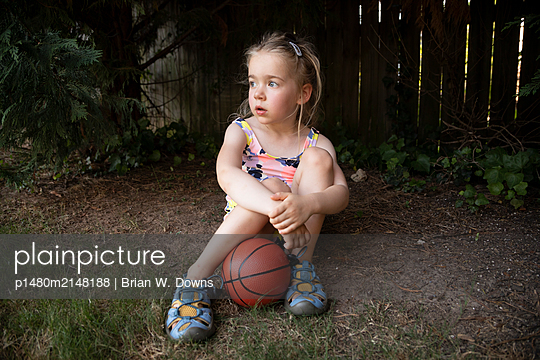 Portrait of a young girl sitting with a basketball in her backyard - p1480m2148188 by Brian W. Downs