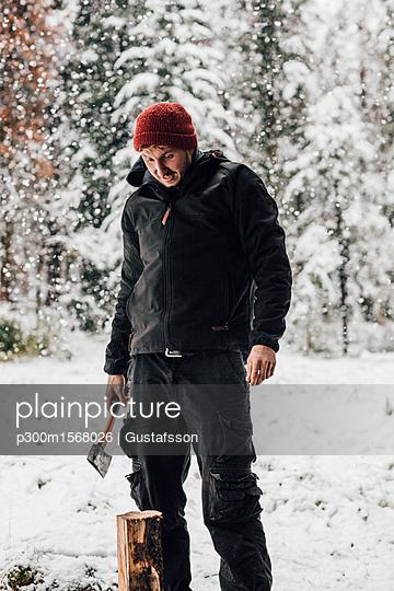 Canada, man chopping wood in snowfall - p300m1568026 by Gustafsson