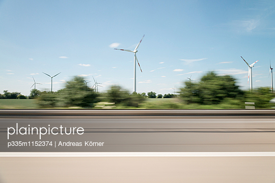 Wind farm along the highway blurred view - p335m1152374 by Andreas Körner