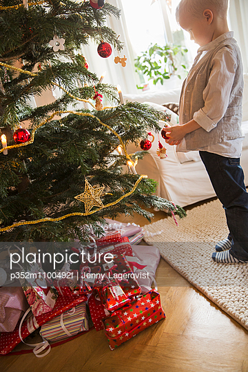 Sweden, Little blonde boy (4-5) standing next to Christmas tree - p352m1100492f by Jenny Lagerqvist
