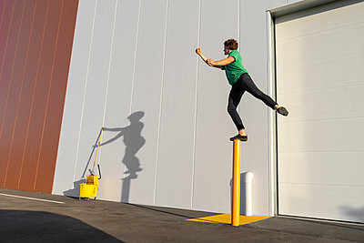 Acrobat standing on pole, casting shadow at cleaning bucket - p300m2012382 von VITTA GALLERY