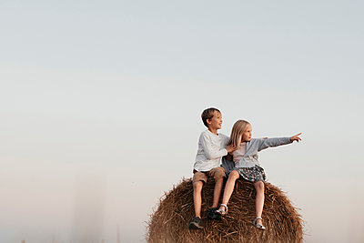 Two kids sitting on the haystack - p300m2143637 by Ekaterina Yakunina