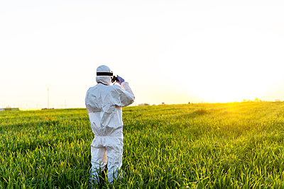 Female scientist researching in field and looking through binoculars at sunset - p300m2170805 by Eloisa Ramos