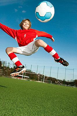 Boy playing football - p608m702103 by Jens Nieth