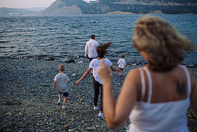 Father, mother, elder daughter and two little sons running on stony beach - p1363m1590987 by Valery Skurydin