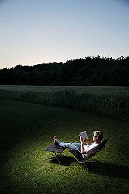 Mann liest ein Buch auf einem Sessel im Grünen - p819m970679 von Kniel Mess