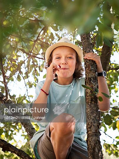 Girl eating cherries on tree - p312m2118992 by Johner