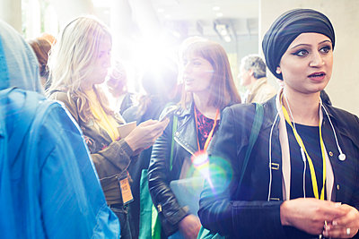 Businesswomen talking at conference - p1023m1583840 by Martin Barraud