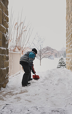 Young boy shovelling snow off of front steps during a snowstorm. - p1166m2095410 by Cavan Images
