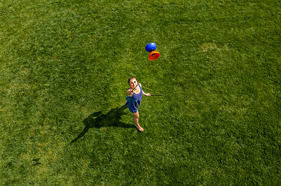 Aerial view of a young woman playing with a Diabolo on a meadow - p300m2114928 by Stefan Schurr