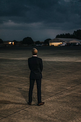 Businessman standing on airfield - p586m1208651 by Kniel Synnatzschke