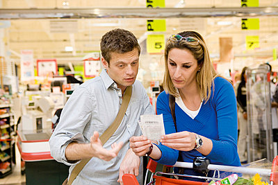 Couple reviewing sales receipt in store - p62314867f by James Hardy