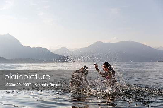 Happy young couple playing in a lake - p300m2042937 by Michela Ravasio