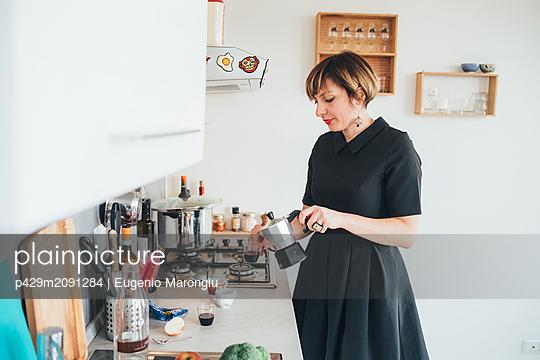 Businesswoman making coffee - p429m2091284 by Eugenio Marongiu