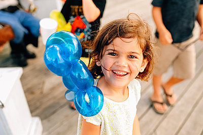 Portrait of smiling girl looking up with parrot balloon on shoulder - p1166m2094924 by Cavan Images