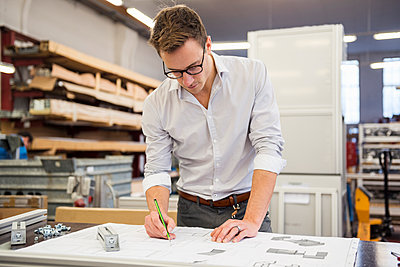 Young businessman in factory working on plan - p300m1563158 by Daniel Ingold