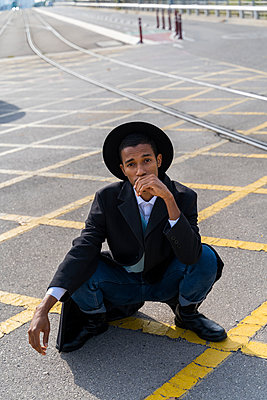 Stylish young man wearing hat crouching on street during sunny day - p300m2239948 by VITTA GALLERY