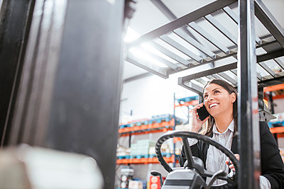 Cheerful female manager talking on mobile phone while operating forklift at warehouse - p300m2267028 by DREAMSTOCK1982