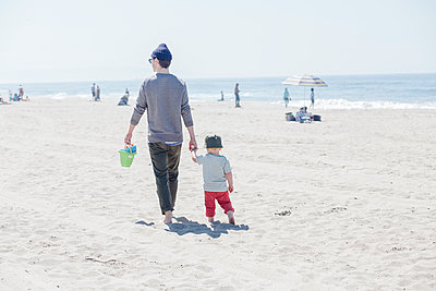 Man holding son hand while walking at beach during sunny day - p300m2287108 by Ashley Corbin-Teich
